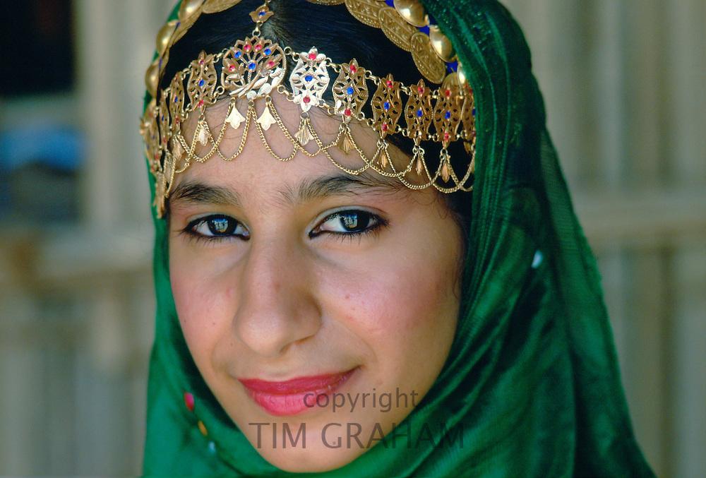 An Omani woman wearing gold jewels and a veil, Nizwa, Oman