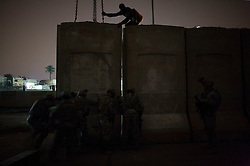 In the middle of the night, engineers with the 82nd Airborne Division and soldiers with Charlie Co. 1-26 Infantry 1st Infantry Division help nudge a segment of a wall being raised, amongst much controversy, around the beleaguered Baghdad Sunni district of Adhamiya on Sunday April 28, 2007.