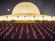 """11 FEBRUARY 2016 - KHLONG LUANG, PATHUM THANI, THAILAND:  The full moon rises above the temple while Buddhist monks pray in their seats on the pagoda during the Makha Bucha Day service at Wat Phra Dhammakaya.  Makha Bucha Day is a public holiday in Cambodia, Laos, Myanmar and Thailand. Many people go to the temple to perform merit-making activities on Makha Bucha Day, which marks four important events in Buddhism: 1,250 disciples came to see the Buddha without being summoned, all of them were Arhantas, or Enlightened Ones, and all were ordained by the Buddha himself. The Buddha gave those Arhantas the principles of Buddhism. In Thailand, this teaching has been dubbed the """"Heart of Buddhism."""" Wat Phra Dhammakaya is the center of the Dhammakaya Movement, a Buddhist sect founded in the 1970s and led by Phra Dhammachayo. Makha Bucha Day is one of the most important holy days on the Thai Buddhist calender.     PHOTO BY JACK KURTZ"""