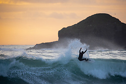 © Licensed to London News Pictures. 12/12/2020. Penzance, UK. Surfers catch waves at sunset at Praa Sands beach in Cornwall. Photo credit : Tom Nicholson/LNP