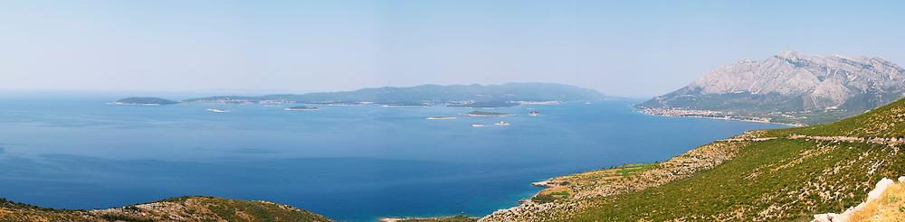 Wide panoramic View over the Orebic village town and the Sveti Ilija mountain, dark blue sea towards Korculanski Kanal and the Korcula island. Peljesac Peninsula. Orebic town. Peljesac peninsula. Dalmatian Coast, Croatia, Europe.