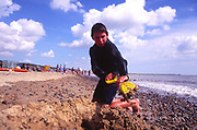 AMHJE7 Boy digging sand Walberswick beach Suffolk England