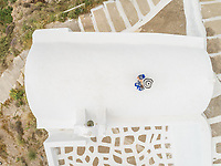 Aerial view woman walking on the roof on Santorini traditional house, Greece.