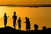 Girls take a break from washing clothes and dishes in the Niger river at sunset in the W. African village of Kouakourou, Mali. Material World Project.
