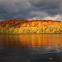 """""""Floating Oak Leaf""""<br /> <br /> A lone fallen oak leaf floats on the water as storm clouds pass overhead. Sunlight shines brightly on the peak fall foliage casting colorful reflections on the water!!<br /> <br /> Autumn Landscapes by Rachel Cohen"""