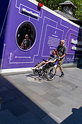 A man pushes a woman in a wheelchair past a purple hoarding that screens off refurburshment works in the West End's Leicester Square, on 16th July 2021, in London, England.