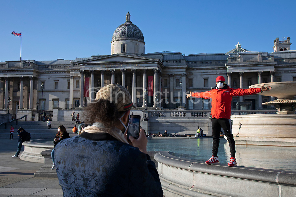 Tourist has his photo taken wearing a face mask in a Trafalgar Square empty and almost deserted due to the Covid-19 outbreak social distancing on what would normally be a busy, bustling day with hoards of people out to shop and socialise on 22nd March 2020 in London, England, United Kingdom. Coronavirus or Covid-19 is a new respiratory illness that has not previously been seen in humans. While much or Europe has been placed into lockdown, the UK government has announced more stringent rules as part of their long term strategy, and in particular social distancing.