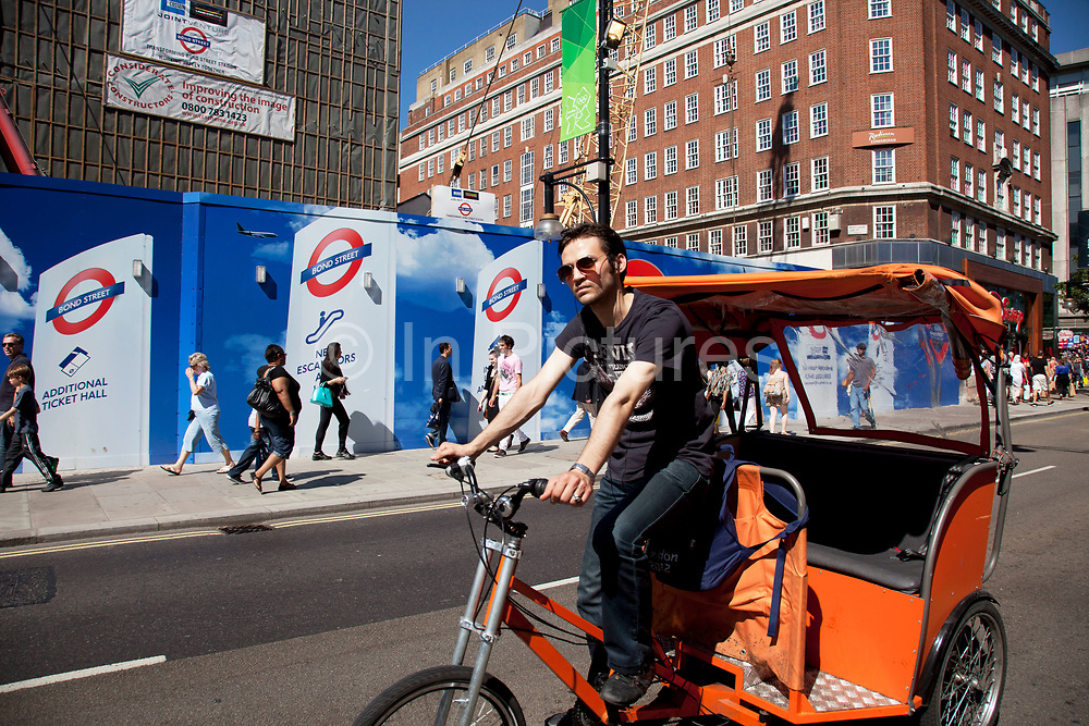 Cycle taxi stops outside the redevelopment of Bond Street underground station in central London, UK. People pass outside a colourful hoarding covering one of the exits to the tube station as new escalators are being installed to improve the public transport system.
