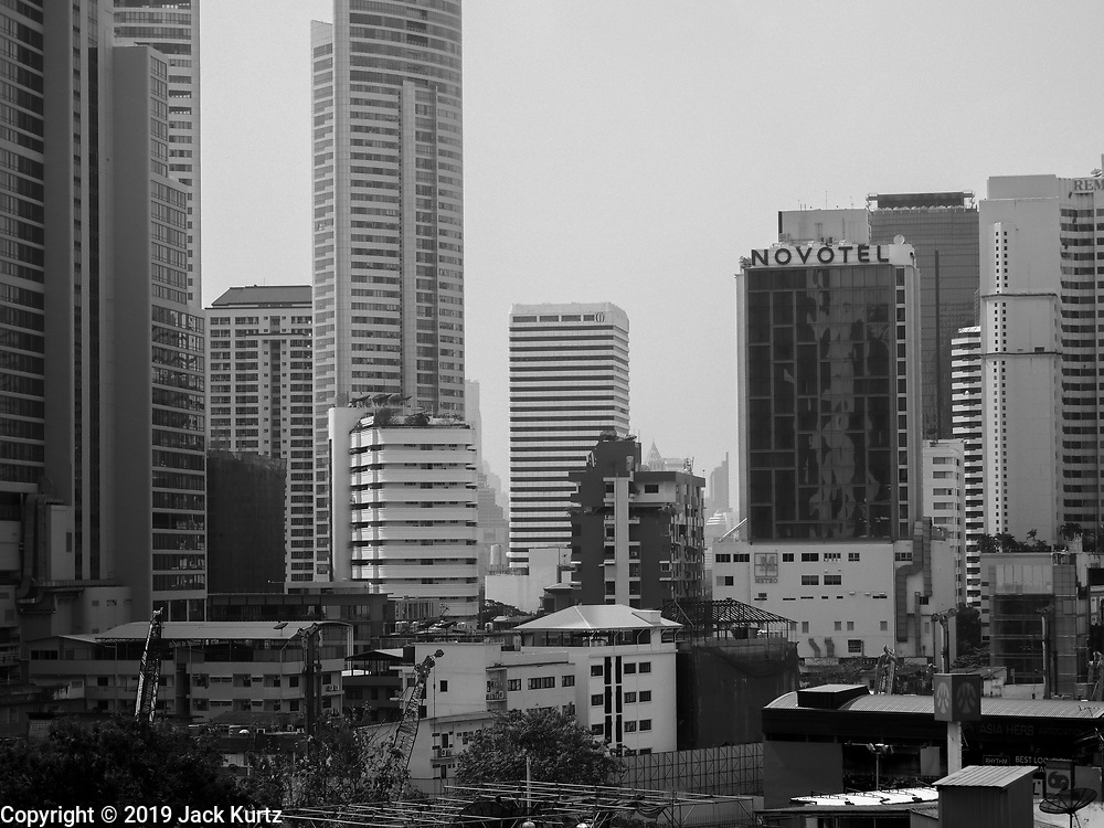 "14 JANUARY 2019 - BANGKOK, THAILAND:       Air pollution obscures the skyline in central Bangkok looking down Sukhumvit Road. Bangkok has been blanketed by heavily polluted air for almost a week. Monday morning, the AQI (Air Quality Index) for Bangkok  was 182, higher than New Delhi, Jakarta, or Beijing. The Saphan Kwai neighborhood of Bangkok recorded an AQI of 370 and the Lat Yao neighborhood recorded an AQI of 403. An AQI above 50 is considered unsafe. Public health officials have warned people to avoid ""unnecessary"" outdoor activities and wear breathing masks to filter out the dust.      PHOTO BY JACK KURTZ"