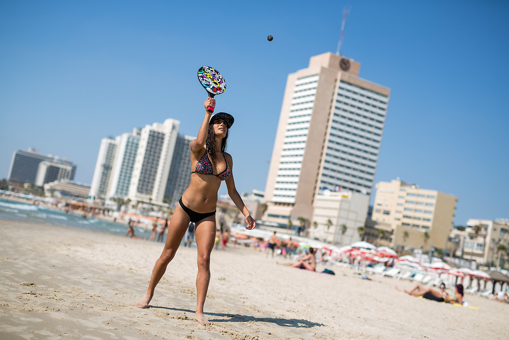 An Israeli woman plays 'Matkot', or beach paddleball which is often referred to as the country's national sport, at Frishman Beach, in Tel Aviv, Israel, on July 21, 2015.
