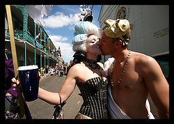 Feb 28th, 2006. New Orleans, Louisiana. Mardi Gras Day, Fat Tuesday. Crowds and faces in the crowd pack Chartres Street in the French Quarter for the annual St Anne's day parade, guaranteed to be awash with mainly locals out for an outrageous day out. A couple kiss in the French Quarter.