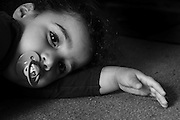 Young boy of two resting on his arm with pacifier in mouth