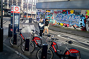 Santander rental bikes await their next riders, in front of young women walking through Shoreditch where graffiti covers the exterior of a former office property, on 26th February 2021, in London, England.