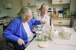 Occupational therapist carrying out a functional assessment on stroke unit observing patient making a cup of tea,