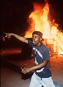 Mark Craig chants near a burning guard shack in front of the Los Angeles Police Department's Parker Center as riots break out after the verdict was announced in the Rodney King case in 1992.