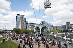 London, UK. 5th June, 2021. Environmental activists and local residents pass beneath the Emirates Air Line cable car as they protest against the construction of the Silvertown Tunnel. Campaigners opposed to the controversial new £2bn road link across the River Thames from the Tidal Basin Roundabout in Silvertown to Greenwich Peninsula argue that it is incompatible with the UK's climate change commitments because it will attract more traffic and so also increased congestion and air pollution to London's most polluted borough.