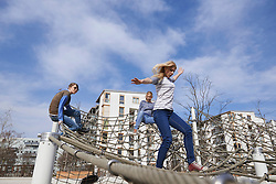 Three friends playing on climbing net in playground, Munich, Bavaria, Germany