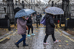 © Licensed to London News Pictures. 07/12/2017. London, UK. People brave strong winds and heavy rain outside Downing Street in central London as Storm Caroline approaches Britain. Photo credit: Rob Pinney/LNP