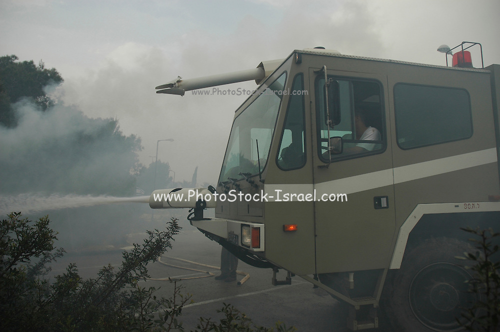 Israel, Haifa Carmel Mountain Forest, A fire engine cannon spraying water on the flames