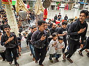 24 OCTOBER 2015 - YANGON, MYANMAR: Shia men arrive at Mogul Mosque after a procession during Ashura observances in Yangon. Ashura commemorates the death of Hussein ibn Ali, the grandson of the Prophet Muhammed, in the 7th century. Hussein ibn Ali is considered by Shia Muslims to be the third imam and the rightful successor of Muhammed. He was killed at the Battle of Karbala in 610 CE on the 10th day of Muharram, the first month of the Islamic calendar. According to Myanmar government statistics, only about 4% of the population is Muslim. Many Muslims have fled Myanmar in recent years because of violence directed against Burmese Muslims by Buddhist nationalists.    PHOTO BY JACK KURTZ