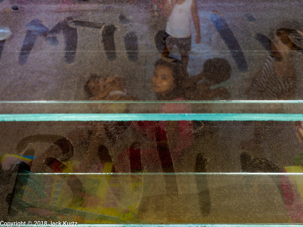 24 JANUARY 2018 - LIGAO, ALBAY, PHILIPPINES: Children's names written in volcanic dust on the windows in a school being used as an evacuation center. 1,849 people from the volcano are staying at the school. The Mayon volcano continued to erupt Tuesday night and Wednesday forcing the Albay provincial government to order more evacuations. By Wednesday evening (Philippine time) more than 60,000 people had been evacuated from communities around the volcano to shelters outside of the 8 kilometer danger zone. Additionally, ash falls continued to disrupt life beyond the danger zones. Several airports in the region, including the airport in Legazpi, the busiest airport in the region, are closed indefinitely because of the amount of ash the volcano has thrown into the air.    PHOTO BY JACK KURTZ