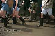 Party people in wellies work their way through mud and puddles at the Glastonbury Festival 22th July 2016, Somerset, United Kingdom.  The festival in 2016 turned out to be the muddiest in years. The Glastonbury Festival runs over 3 days and has 3000 acts, including music, art and performance and approx. 150.000 attend the anual event.