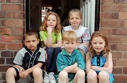 Group of children sitting on doorstep,