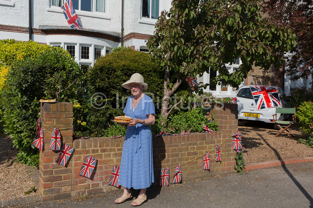 As the Coronavirus lockdown continues over the May Bank Holiday, the nation commemorates the 75th anniversary of VE Day Victory in Europe Day, the day that Germany officially surrendered in 1945 and in Dulwich, neighbours and residents emerge from their homes to party while still observing social distancing rules. A local lady resident shares home-made cake with neighbours, on 8th May 2020, in London, England.