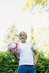 Portrait of smiling young boy with ball