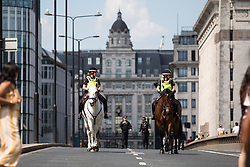 © Licensed to London News Pictures. 03/06/2018. London, UK. Police horses are seen riding down London Bridge on the anniversary of the London Bridge and Borough Market terror attacks. A series of events have taken place throughout the day, including a service of commemoration at Southwark Cathedral, the planting of an olive tree in the Cathedral grounds, a minute's silence at 4:30pm and the laying of flowers.  Photo credit : Tom Nicholson/LNP