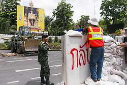 © Licensed to London News Pictures. 23/05/2014. An army officer directs council workers to dismantle barricades at a PDRC protest site in front of a large portrait of the Thai King in Bangkok Thailand. Thailand's army said on May 23 that 155 prominent figures, including Yingluck and ousted government leaders, were banned from leaving the country without permission following a military coup.  Photo credit : Asanka Brendon Ratnayake/LNP