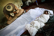 Azibullah, 30, cries next to the dead body of his wife, Qamar, center,  a 26-year-old tuberculosis patient who died of postpartum complications two weeks after the delivery, and her baby, in their house in the village in Shohada district in Badakshan province, Afghanistan, Monday, May 21, 2007.