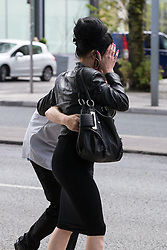"© Licensed to London News Pictures . 13/05/2015 . Manchester , UK . Chantelle Partington (near side) and Ian Oldham (hiding from camera behind Partington) outside Manchester Magistrates Court today (13th May 2015) . The pair are jointly charged with a Section 4a Public Order Offence , namely using threatening, abusive, insulting words or behaviour to cause harassment alarm or distress , after Jean Claude Manseau suffered homophobic verbal abuse on a Manchester City Centre tram on 1st November 2014 . The abuse is reported to have been prompted by Manseau and his friend Jake Heaton singing a tune from the show "" Wicked "" . Following this they were physically assaulted on the street by between 10 and 20 people , none of whom have been identified . The incident prompted a campaign by the Manchester Lesbian and Gay Chorus which saw protesters singing on City Centre trams under the banner of "" Safe to Sing "" . Photo credit : Joel Goodman/LNP"