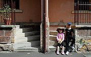 Two children (6 years old and 10 years old) sitting on stone steps to terraced houses. The Rocks, Sydney, Australia