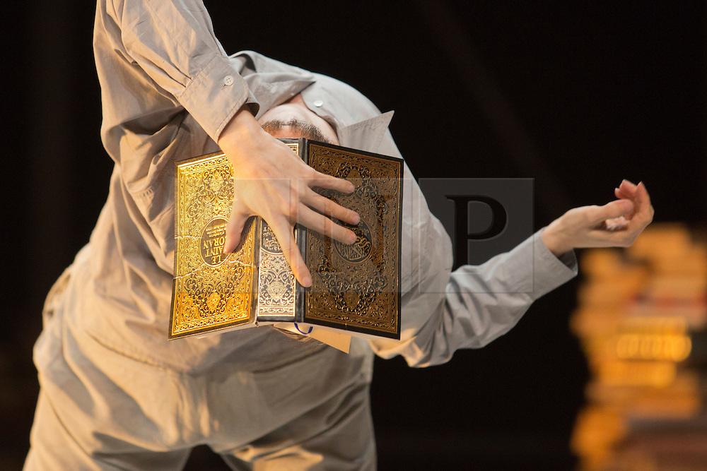 """© Licensed to London News Pictures. 24/01/2014. London, England. Pictured: Sidi Larbi Cherkaoui dances with the Koran. Belgian dancer/choreographer Sidi Larbi Cherkaoui's work """"Apocrifu"""" uses the language of the body to explore apocryphal religious texts, accompanied by the polyphonic singing from the all-male Corsican vocal ensemble """"A Filetta"""". Dancers: Sidi Larbi Cherkaoui, Dimitri Jourde and Yasuyuki Shuto. Performances at the Queen Elizabeth Hall, Southbank Centre from 24th to 25the January 2014. Photo credit: Bettina Strenske/LNP"""