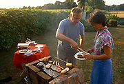 A middle-aged husband serves a plate of meat to his wife from the family home-made BBQ in the back garden on a summers afternoon, in June 1989, in Wrington, North Somerset, England.
