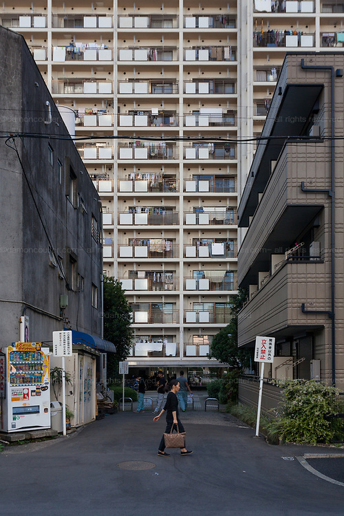 A woman walks past tall apartment buildings near Zoshigaya in Tokyo, Japan. Friday September 28th 2018