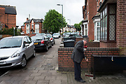 Man sweeping up outside the front of his property in Birmingham, England, United Kingdom.