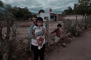 """Kevin (7) en brazos de su madre Gabriela (24). Detrás de ellos su hermanito Brian (5). Ellos viven en un pequeño pueblo en la provincia de La Rioja, Argentina. A 1150 km de distancia con la Capital Federal. Kevin nació con una condición patológica conocida como """"Huesos de Cristal"""" (Osteogénesis imperfecta). Sus huesos se rompen con facilidad y sufren deformaciones óseas debido a una alteración en el gen que fabrica la proteína de colágeno. Su madre Gabriela no tuvo ningún diagnóstico prenatal, a pesar de haberse hecho todos los estudios de control y ecografías. El niño nació con los huesos de sus dos brazos y el fémur quebrados. Al día de hoy, lleva un total de 33 quebraduras en todo su cuerpo. Cuando se quiebra sólo puede utilizar vendas y permanecer en cama inmovilizado durante semanas. Su madre es quien cuida de él y lo asiste en todas y cada una de sus necesidades. """"Kevin pasa mucho dolor cada vez que se quiebra alguno de sus huesos. A veces se despierta por las noches y dice que prefiere morir."""" -Dice su madre- El Sistema de Salud Público nunca cubre sus tratamientos ni el personal asistente de apoyo. Kevin sólo recibe la medicación de manera intermitente."""