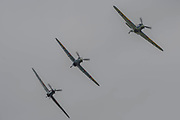 Three of the Six Hawker Hurricanes fly in formation around the airfield and then come into land - Duxford Battle of Britain Air Show taking place during IWM (Imperial War Museum) Duxford's centenary year. Duxford's principle role as a Second World War fighter station is celebrated at the Battle of Britain Air Show by more than 40 historic aircraft taking to the skies.