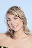 portrait in studio on a blue background of a young blond caucasian smiling and expressive woman