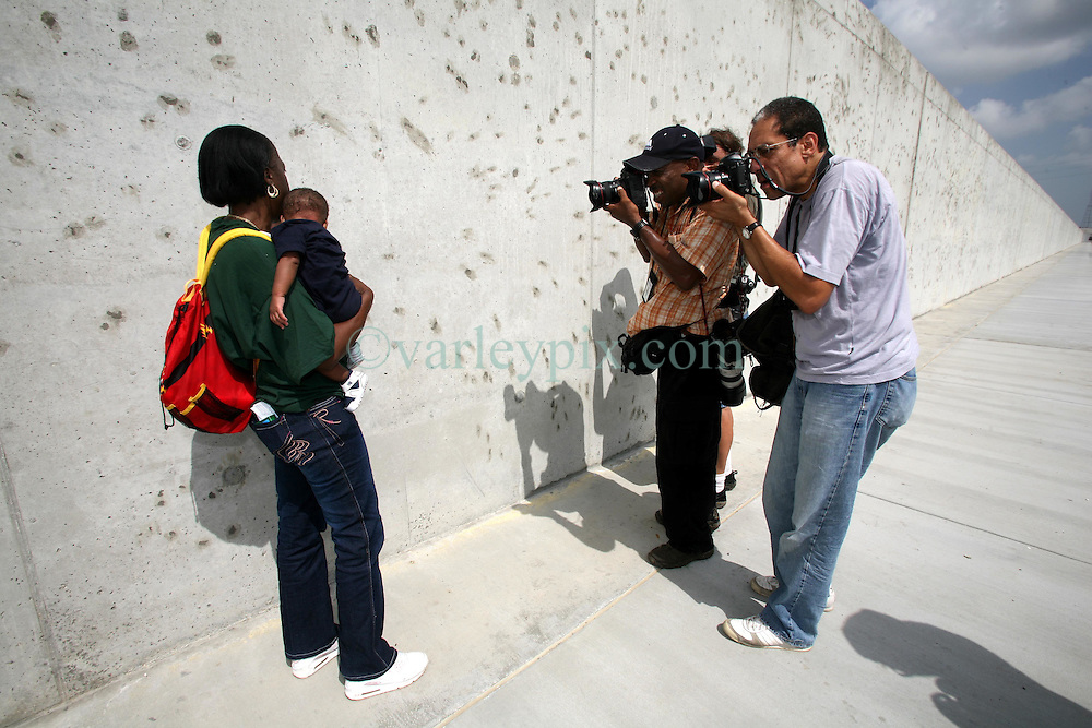 29 August 2006. New Orleans, Louisiana. Lower 9th ward. <br /> The media photograph Chevelle Washington (who lost her uncle) and her grandson David (5mts) as she stands crying beside the newly renovated industrial canal levee flood wall. Civilians gathered at the site of the breach of the industrial canal for the Great Flood commemoration and memorial ceremony to 'honor and remember our loved ones who have passed.' People came to mark the anniversary of devastating hurricane Katrina at the site where the now repaired and allegedly in theory stronger levee flood wall. The levee breached along the industrial canal at the point where people gathered, needlessly killing hundreds of innocent civilians in the worst engineering disaster in US history.<br /> Photo Credit©; Charlie Varley/varleypix.com