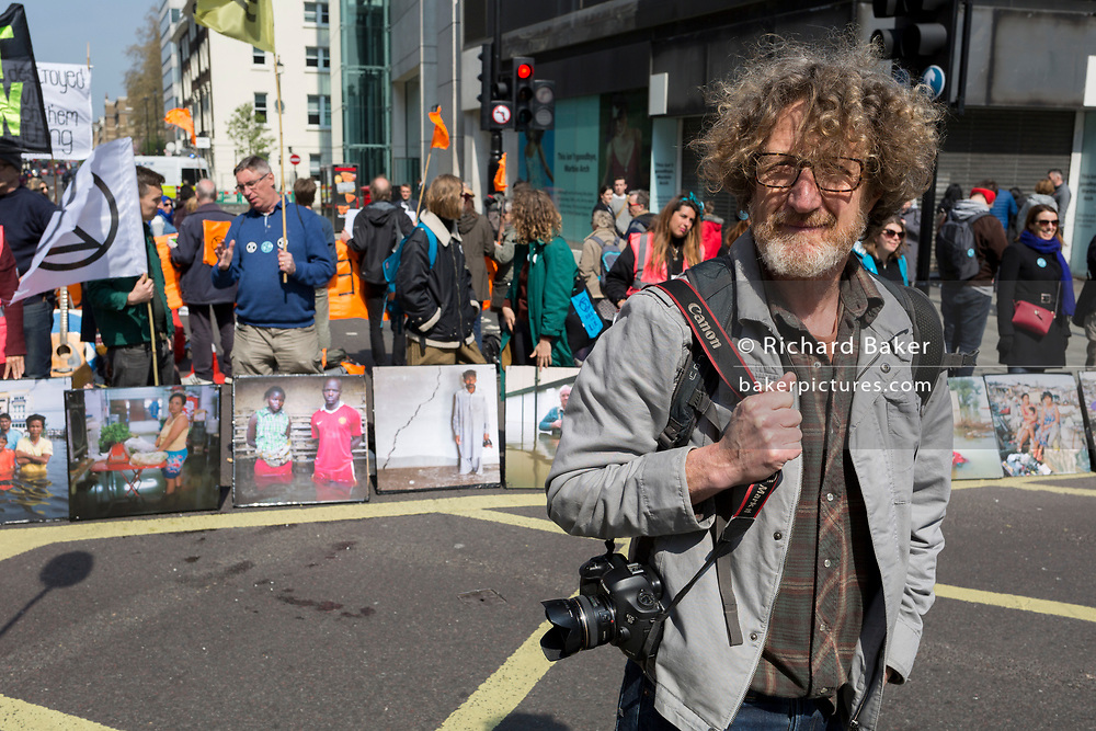 Photographer Gideon Mendel and some of his flood victim portraits 'Drowning World' during the climate Change protest with Extinction Rebellion blocking Oxford Street and simultaneously stop traffic across central London including Marble Arch, Piccadilly Circus, Waterloo Bridge and roads around Parliament Square, on 15th April 2019, in London, England.