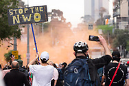 Orange smoke from a flare that was lit during the demonstration is seen as they march down the street during the Freedom protest on October 23, 2020 in Melbourne, Australia. Freedom protests are being held in Melbourne in response to the governments COVID-19 restrictions and continuing removal of liberties despite new cases being on the decline. Victoria recorded a further 1 new cases overnight along with no deaths recorded.(Photo by Mikko Robles/Speed Media)