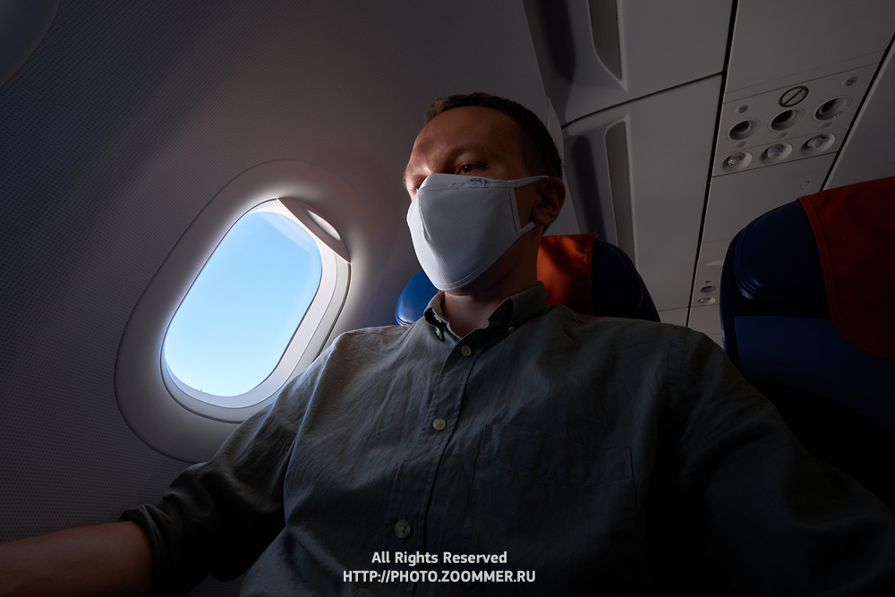 Passenger wearing mask in airplane