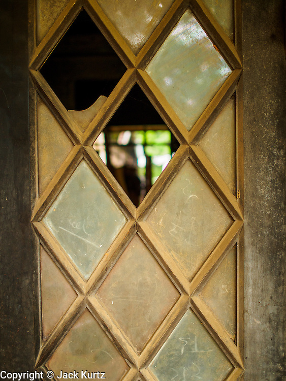 07 JUNE 2014 - YANGON, MYANMAR: Broken windows in a doorway at the Pegu Club. The Pegu Club in Yangon was the Officers' Club for the British Army when Myanmar was the British colony of Burma. The club, principally made of teak, is now abandoned and in decay. Squaters have moved into the parts of the complex still standing. Yangon has the highest concentration of colonial style buildings still standing in Asia. Efforts are being made to preserve the buildings but many are in poor condition and not salvageable.    PHOTO BY JACK KURTZ