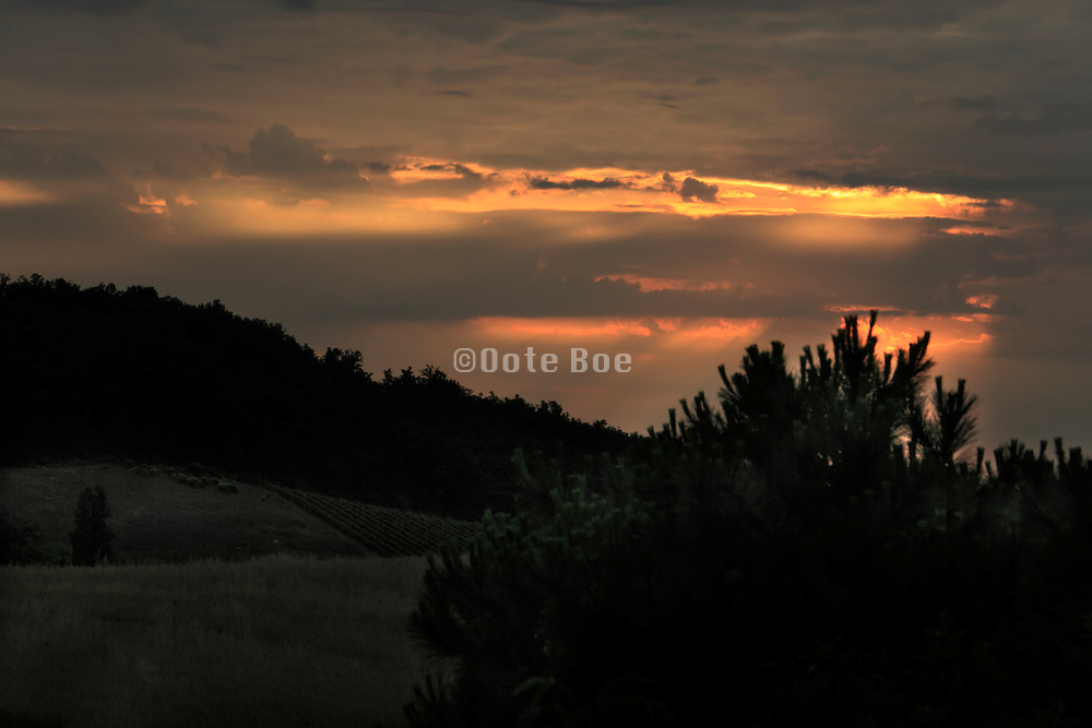 rays of sunlight with clouds and rural hilly landscape France Languedoc Aude