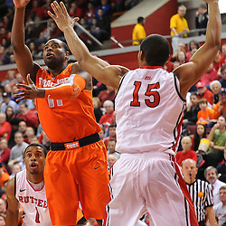 Syracuse Orange guard Scoop Jardine (11) lays a basket in over Rutgers Scarlet Knights forward/center Derrick Randall (15) during first half NCAA Big East basketball action between #2 Syracuse and Rutgers at the Louis Brown Athletic Center. Syracuse leads 40-34 at halftime.