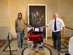 "© Licensed to London News Pictures. 27/08/2014; Bristol, UK.  'No Comment' (person on left) and Dennis Stinchcombe MBE of Broad Plain Working with Young People club with a 'Thanks Banksy"" sign and the Banksy piece 'Mobile Lovers' which has been sold for £403,000 by Mary McCarthy of MM Contemporary Arts to a private buyer on behalf of the club.  The artwork was placed near to the Riverside Project at the Broad Plain club run by Dennis Stinchcombe MBE.  There was a dispute between Denis and the Mayor of Bristol George Ferguson over the ownership of the artwork which was resolved when Banksy sent a letter to the club saying the artwork was theirs to do with what they wished.  The money from the sale will help fund the continuing activities of the club.<br /> Photo credit: Simon Chapman/LNP"