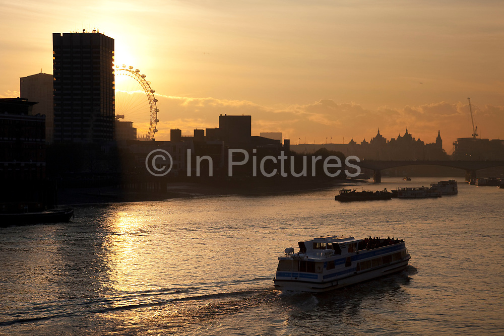 Sun setting behind a tall building, looking over the River Thames as boats pass by towards the skyline of the Southbank and the London Eye.
